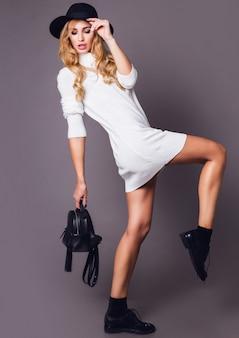 Porträt der jungen eleganten blonden frau im hut und im stilvollen weißen winterpullover