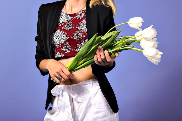 Porträt der jungen eleganten frau mit hellem make-up und dunklem blazer, die weiße blumen hält