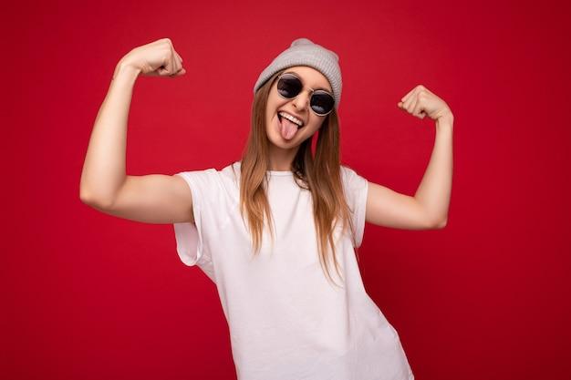 Porträt der jungen emotionalen positiven glücklichen hübschen dunkelblonden weiblichen person, die lässiges weiß trägt