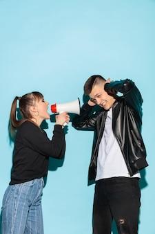 Porträt der jungen emotionalen studentin mit megaphon