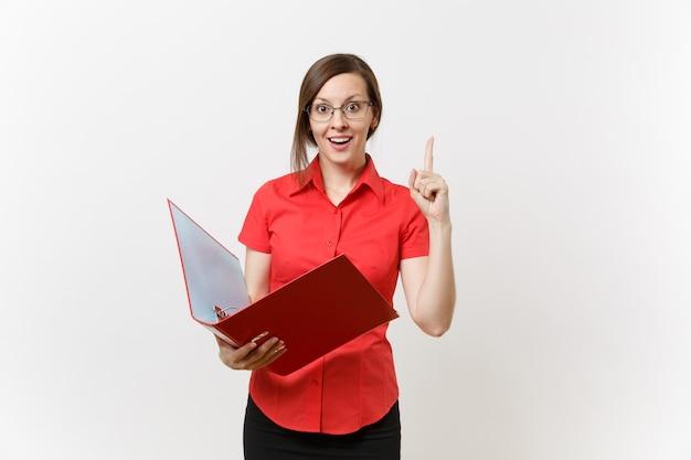 Porträt der jungen erfolgreichen geschäftslehrerfrau im roten hemd, gläser, die ordner mit den papierarbeitsdokumenten lokalisiert auf weißem hintergrund halten. bildungsunterricht im hochschulkonzept.