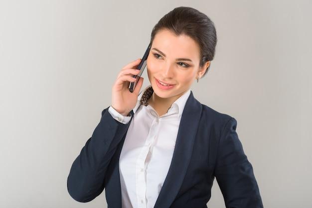 Porträt der jungen ernsten frau im geschäftsoutfit, das am telefon auf dem grauen hintergrund spricht
