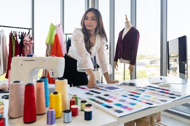 Porträt der jungen erwachsenen asiatischen modedesignerin, die von zu hause mit farbpalette als unternehmerin in ihrem atelierstudio arbeitet. verwendung für unternehmer small business startup-konzept.