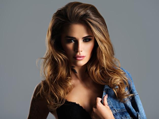 Porträt der jungen erwachsenen ausdrucksstarken frau mit braunen haaren. schönes model, das im studio aufwirft.