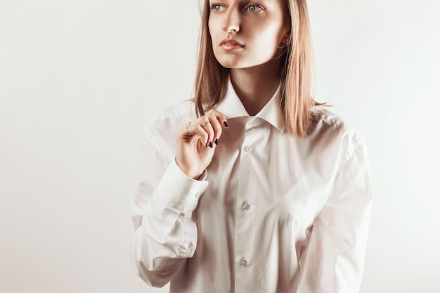 Porträt der jungen erwachsenen frau, die kragen des weißen hemdes mit ihrer hand hält,