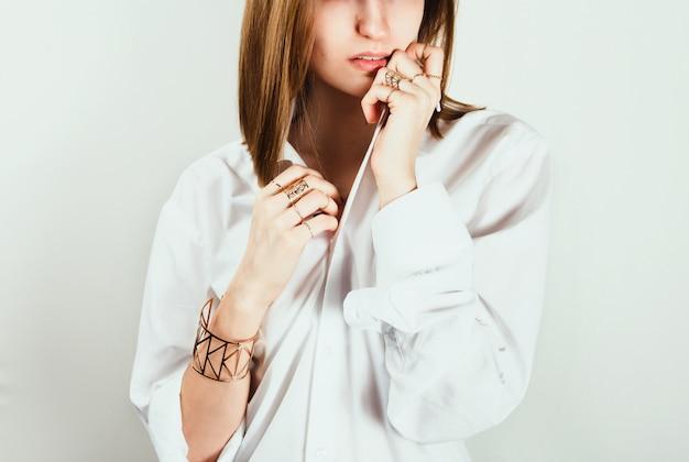 Porträt der jungen erwachsenen weißen frau im weißen hemd, das eine seite ihres gesichts mit einem hemd bedeckt. .