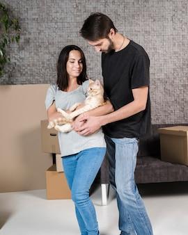 Porträt der jungen familie, die eine katze hält