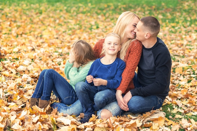 Porträt der jungen familie, die im herbstlaub sitzt