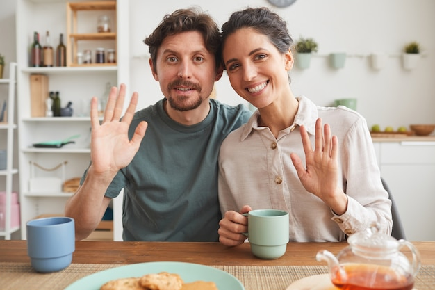 Porträt der jungen familie, die lächelt und winkt, während sie am tisch sitzt und in der küche frühstückt