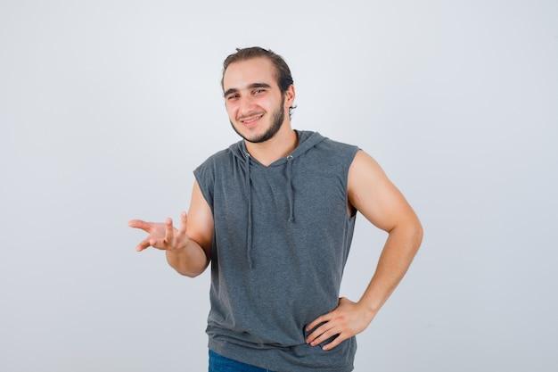 Porträt der jungen fit männlichen streckenden hand in richtung kamera im ärmellosen kapuzenpulli und freudige vorderansicht schauend