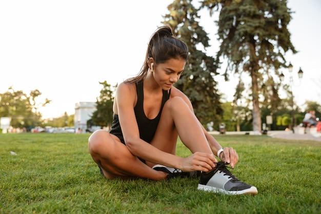 Porträt der jungen fitnessfrau, die ihre schnürsenkel bindet