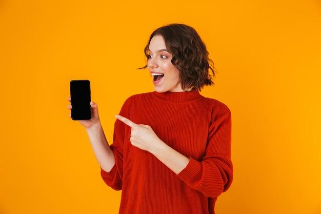 Porträt der jungen frau 20s, die pullover hält und smartphone demonstriert, während isoliert über gelb stehen