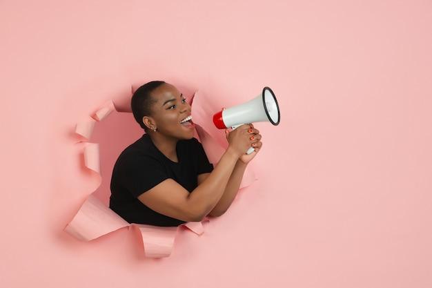 Porträt der jungen frau auf rosa zerrissenem durchbruchhintergrund