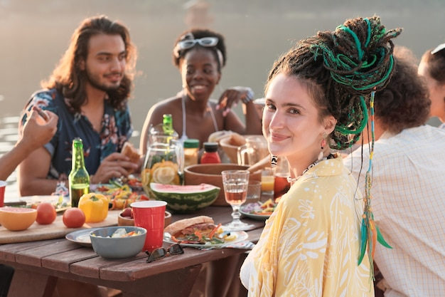 Porträt der jungen frau beim abendessen am tisch zusammen mit ihren freunden im freien