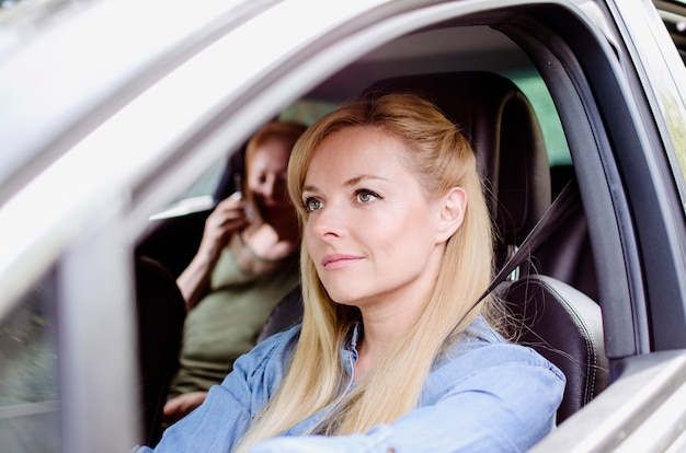 Porträt der jungen frau, das ältere alte frau auf dem rücksitz des autos fährt