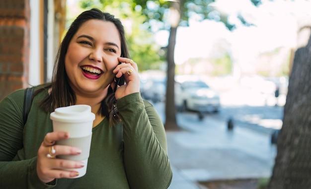 Porträt der jungen frau der übergröße, die am telefon spricht, während sie eine tasse kaffee draußen in der straße hält.