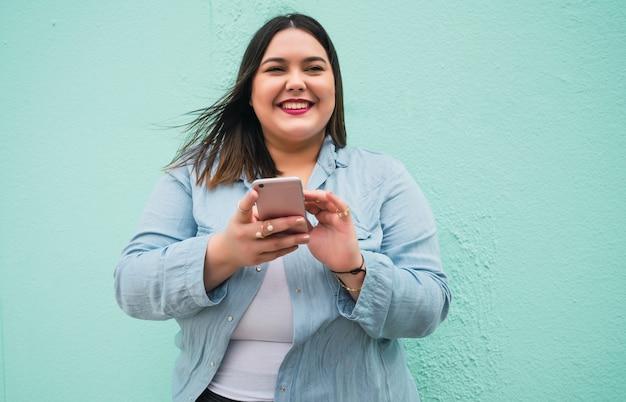 Porträt der jungen frau der übergröße, die textnachricht auf ihrem handy im freien schreibt.