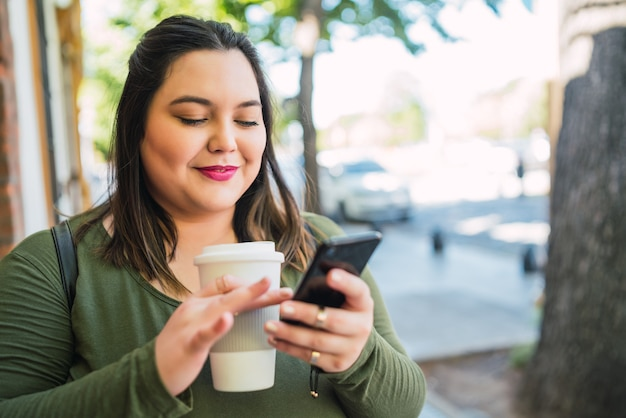 Porträt der jungen frau der übergröße, die textnachricht auf ihrem handy tippt, während eine tasse kaffee draußen an der straße hält
