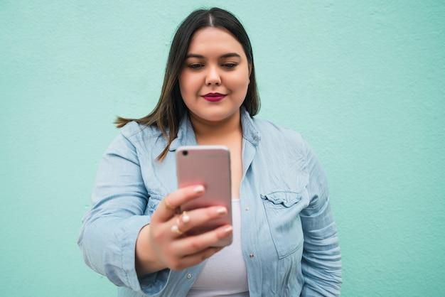 Porträt der jungen frau der übergröße, die videoanruf auf ihrem handy draußen gegen hellblau tut