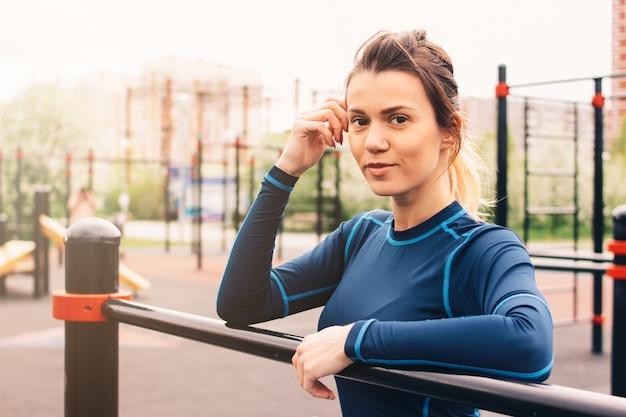 Porträt der jungen frau des attraktiven sitzes im sportabnutzungsrest auf dem straßentrainingsbereich.