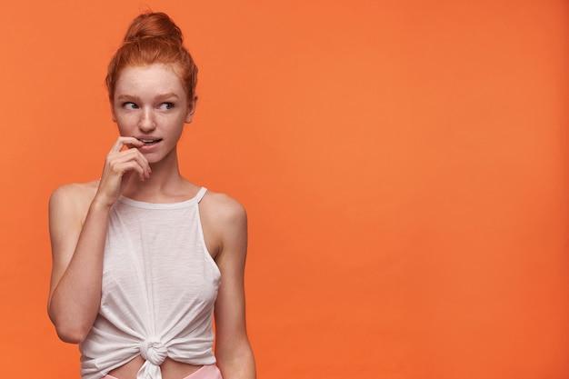 Porträt der jungen frau des gorgeus mit dem foxy haar gekämmt im brötchen, das über orange hintergrund aufwirft, mit interesse beiseite schaut und zeigefinger auf unterlippe hält, sanft lächelnd