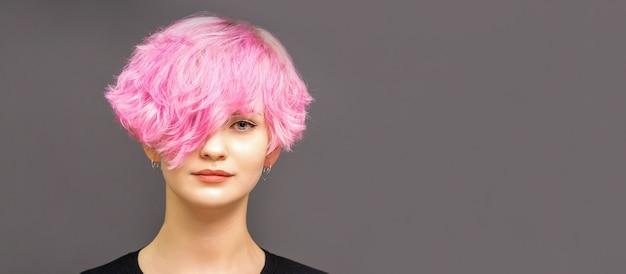 Porträt der jungen frau des modemodells mit stilvoll gefärbtem rosa haar in den schwarzen kleidern auf dunklem hintergrund