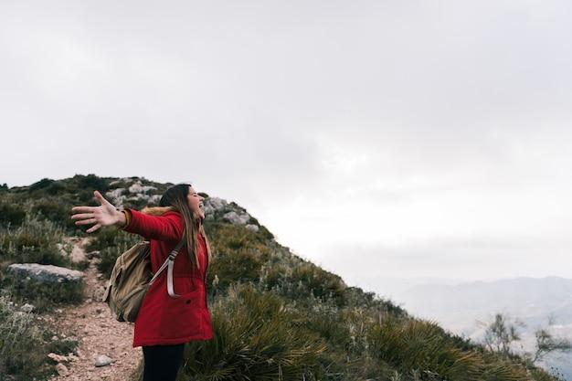 Porträt der jungen frau des überglücklichen sitzes, die auf dem berg mit ihrem ausgestreckten arm steht