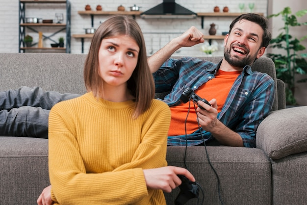 Porträt der jungen frau des umkippens, die nahe dem lächelnden jungen zujubelnden mann beim spielen des videospiels sitzt