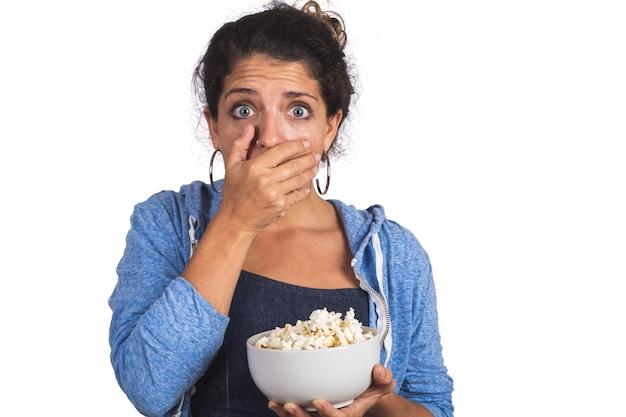 Porträt der jungen frau, die ängstlich schaut, während sie einen film sieht und popcorn auf studio isst. isolierter weißer hintergrund.