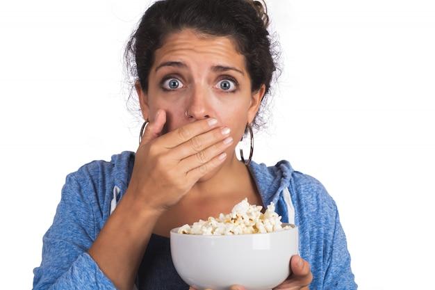 Porträt der jungen frau, die ängstlich schaut, während sie einen film sieht und popcorn auf studio isst.