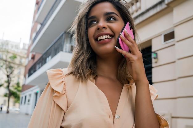 Porträt der jungen frau, die am telefon spricht, während sie draußen auf der straße steht