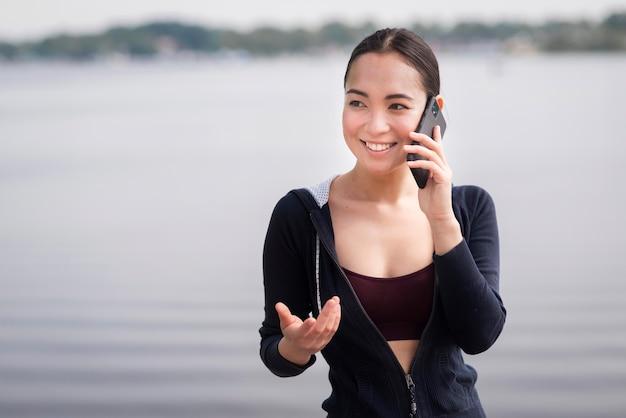 Porträt der jungen frau, die am telefon spricht
