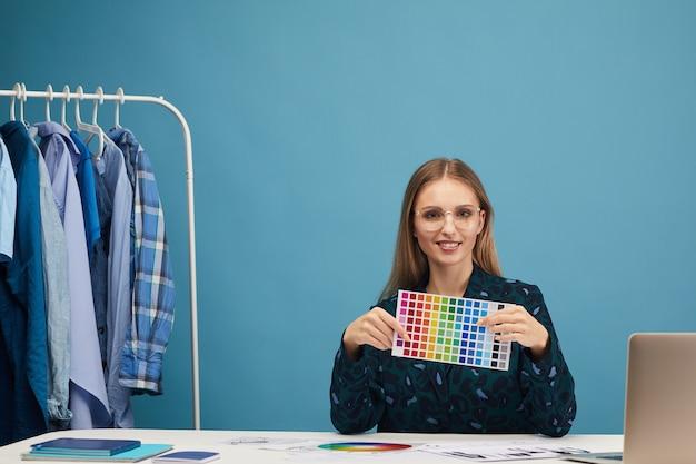 Porträt der jungen frau, die am tisch sitzt und farbiges muster zeigt, während sie im studio arbeitet