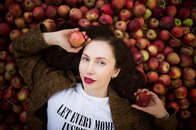 Porträt der jungen frau, die auf einem hügel der roten äpfel liegt. ernte.