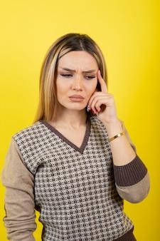 Porträt der jungen frau, die auf gelb steht und schaut.