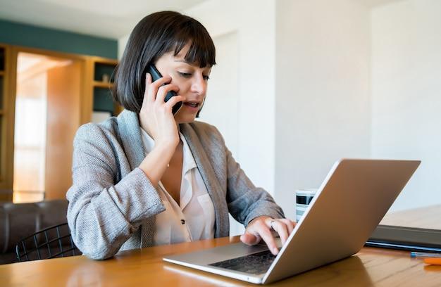 Porträt der jungen frau, die auf ihrem handy spricht und von zu hause mit laptop arbeitet