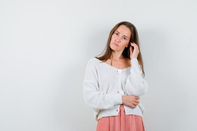 Porträt der jungen frau, die aufwirft, während sie ihr haar in der isolierten strickjacke berührt