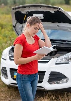Porträt der jungen frau, die bedienungsanleitung bei kaputtem auto liest