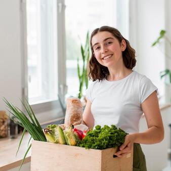 Porträt der jungen frau, die bio-gemüse hält