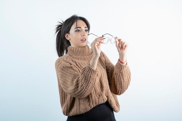 Porträt der jungen frau, die brille auf weißer wand trägt