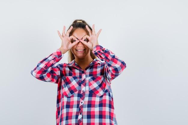 Porträt der jungen frau, die brillengeste im freizeithemd zeigt und fröhliche vorderansicht schaut