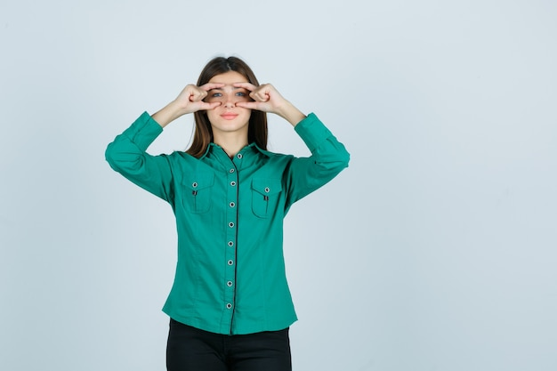 Porträt der jungen frau, die brillengeste in grünem hemd zeigt und fröhliche vorderansicht schaut