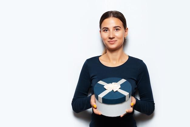 Porträt der jungen frau, die eine blaue geschenkbox hält