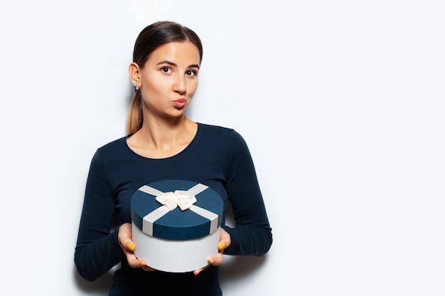 Porträt der jungen frau, die eine geschenkbox hält.