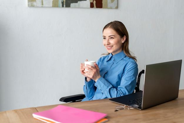 Porträt der jungen frau, die eine tasse kaffee genießt