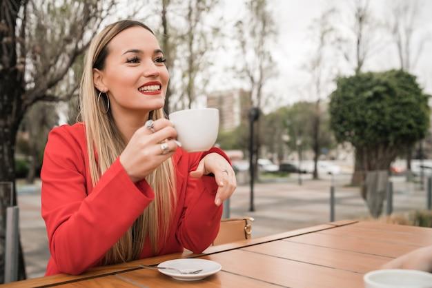Porträt der jungen frau, die eine tasse kaffee im café genießt und trinkt. lifestyle-konzept.