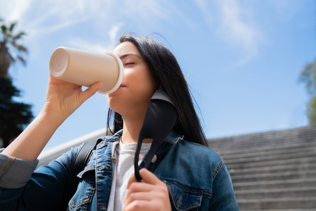 Porträt der jungen frau, die eine tasse kaffee trinkt, während draußen auf der straße steht