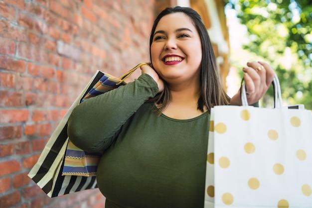 Porträt der jungen frau, die einkaufstaschen draußen auf der straße hält