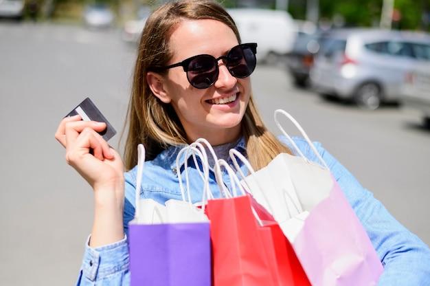 Porträt der jungen frau, die einkaufstaschen hält