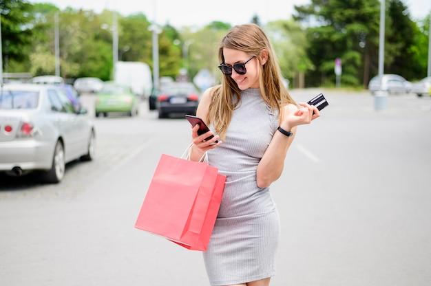 Porträt der jungen frau, die einkaufstaschen trägt